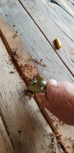 hand scraping a reclaimed oak floor before sanding